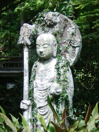 A Japanese religious statue, made of grey stone. The statue holds a ball in one hand and a pole in another. Vines trail over the stone. Trees and bushes form the background. Stock Photo