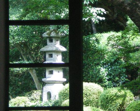 A Japanese stone shrine seen through the frame of a window. The other window is open, looking onto a formal Japanese garden.