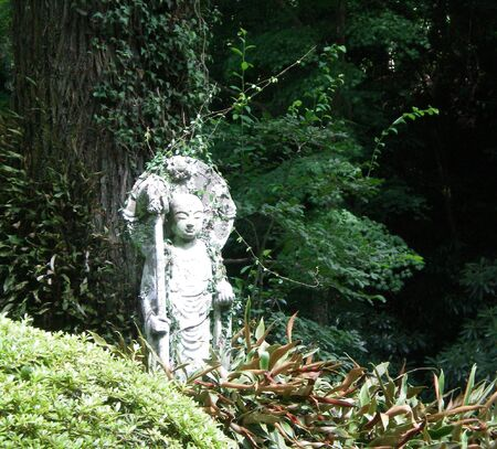 A Japanese stone statue surrounded by bushes and trees. The background is green. Some vines cover the statue. Editorial