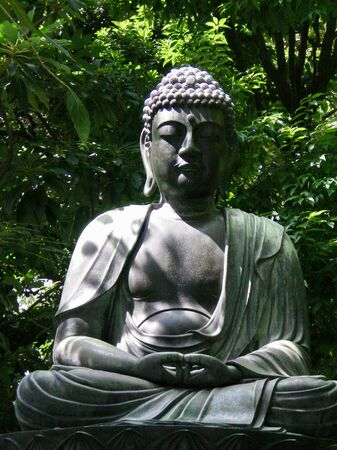 A sitting buddha statue rests against a backdrop of green trees and bushes. The statue is of grey stone, and covered in shadow. The buddha sits in contemplation. Stock Photo
