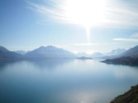 Ještě modré jezero obklopené horami. Sníh je na několika z nich. Tam je modrá obloha s bílými mraky, což se odráží v jezeře. Jezero je opuštěné.