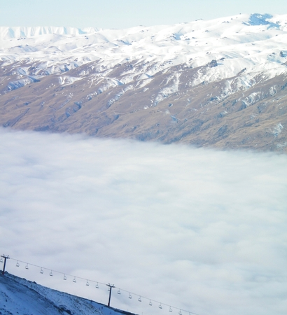 A chairlift rising out of a valley of fog. The chairlift is empty. Mountains covered in snow are in the background. The sky is blue, with no clouds.