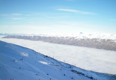 A ski-field above a valley full of clouds. Chairlifts come out of the clouds, and skiers are on the mountain. Snow-covered mountains are in the distance. The sky is blue, with white clouds.
