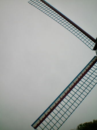 A close-up shot of the sails of a windmill against a grey sky. There is a tree in the lower corner. The sails consist of a wooden lattice.