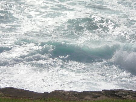 A rock shelf overlooking the sea. The crashing waves have formed whirls of white water and foam.