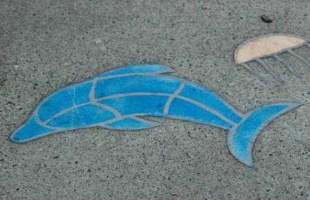 Mosaic in a footpath of a blue dolphin and a cream jellyfish. The surrounding concrete is grey with black and grey pebbles. Stock Photo