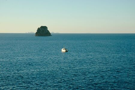 A rock rising out of the ocean towers over a small fishing boat. Calm blue water stretches to the horizon. Some islands can be seen on the horizon. The sky is clear.