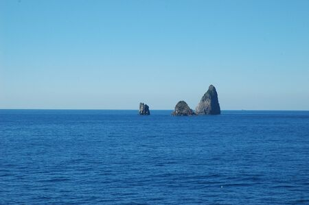 A cluster of three rocks rising from a dark blue ocean. The water is calm. The sky is blue, with no clouds. A tanker can just be seen on the horizon, and a seagull on the water in the foreground.