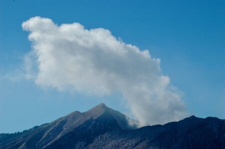 Smoke rising from an active volcano. The mouth of the volcano is jagged and rocky, with some trees further away. The sky is blue, with no clouds. Stock Photo