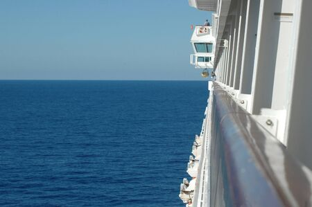 View from a porthole along the railing of a cruise ship to the horizon. A person can be seen on top of the bridge. The ocean is calm. There are no other boats. The sky is clear.