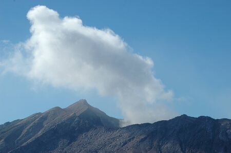 Smoke rising from an active volcano into a clear blue sky. The slopes of the volcano are barren rock. Stock Photo