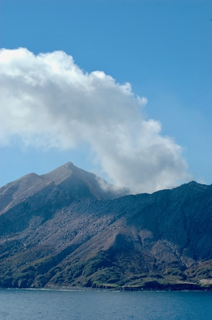 Smoke from a volcano rises against a blue sky. The upper slopes are covered with rocks, with some trees on the  lower slopes. A calm blue ocean is the foreground. Stock Photo