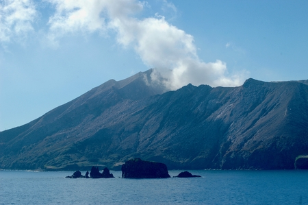 A volcanic island, with smoke rising into a clear blue sky. The water is still and blue, with rocks in the foreground. Stock Photo