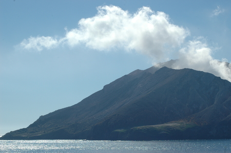 Smoke rising from an active volcano into a clear blue sky. The volcano is surrounded by sparkling blue water.