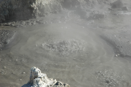 A mud pool with hot, bubbling mud. Steam and smoke rise from the mud. The surrounding rocks are covered in sulphur.