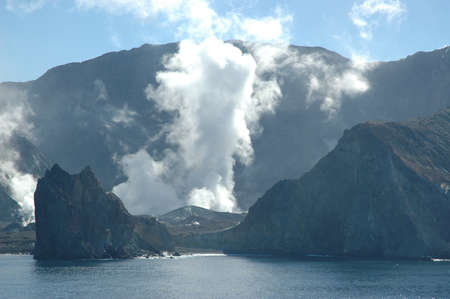 Smoke and steam is rising from the crater of an active volcano. The volcano is an island, and water is in the foreground. The sky is blue with no clouds.