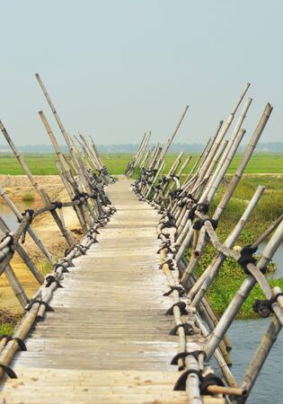 A bamboo bridge bends as it crosses over a river. On the far side are rice paddies. Bamboo poles from the bridge lean to either side. The sky id pale blue, with no clouds.