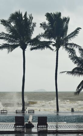 Palm trees swaying in a tropical storm. Waves from the ocean are breaking into a pool. Deck chairs are around the pool. The ocean is brown. An island is on the horizon.