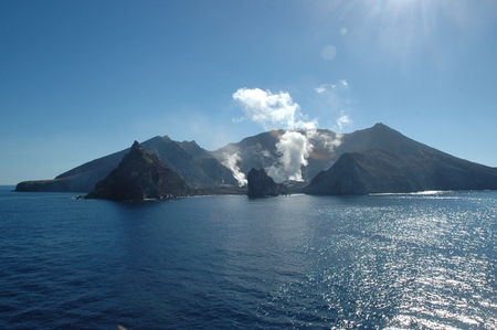 Smoke and steam rising from a volcano. It is on an island surrounded by blue sea. The sea is calm. The sky is blue, with no clouds.