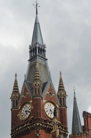 A red and cream brick clock tower is topped with a silver spire. The sky is filled with grey stormy clouds. Stock Photo