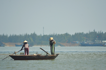 Two people on a traditional Vietnamese fishing boat. The boat has eyes painted at the front. One person is holding a net as the other steers the boat. Large nets and fishing trawlers are in the background. The sky is clear.