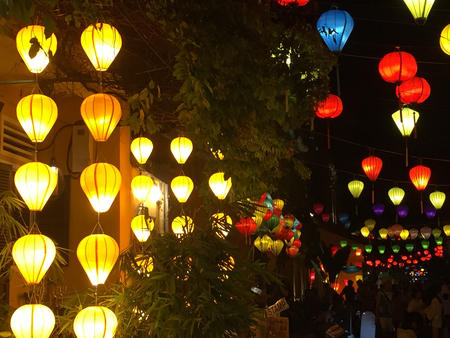 A collection of bright lanterns at night. They are a range of colours, from yellow, red, blue, purple and green. They are in traditional Vietnamese style.