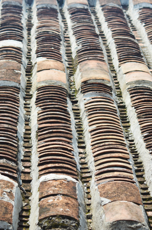 Details of tiles terracotta tiles on a roof in Hoi An, Vietnam. They are traditional is style, being curved and placed in vertical rows, with gaps between them. Stock Photo - 91697867