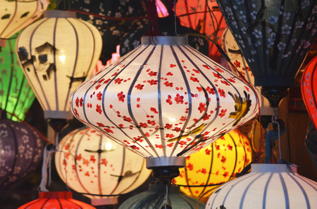 Colorful lanterns on display at a night market. They have been hand-painted, with designs of flowers, birds, and houses. They are in traditional Vietnamese style. Stock Photo
