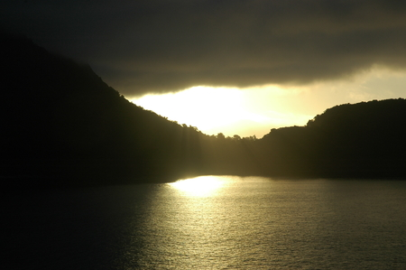 Sunlight falls through a layer of dark clouds onto a bay, turning the water golden. The hills surrounding the water are in shadow.
