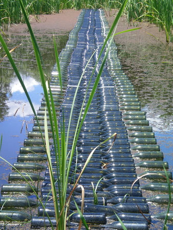 A bridge made of empty wine bottles lies across a pond. The pond is filled with reeds. White clouds are reflected in the water. Stock Photo
