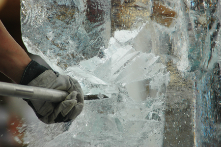 A man is carving an ice-statue from a block of ice. Only his arm can be seen. He is using an ice-pick. Shards of ice are falling from the block.