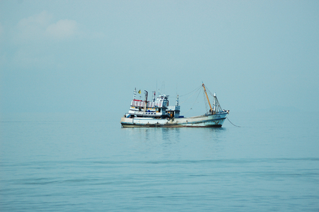 An old rusty fishing boat is anchored at sea. The water is pale blue, as is the sky, so that the horizon can barely be seen. Some faint clouds are visible. The boat is reflected in the water.