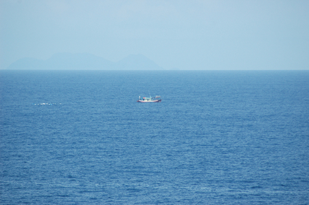A small fishing boat being followed by a flock of seagulls. The boat looks small on the vastness of the ocean. A rocky island is rising from the horizon. The sky is clear blue. Stock Photo