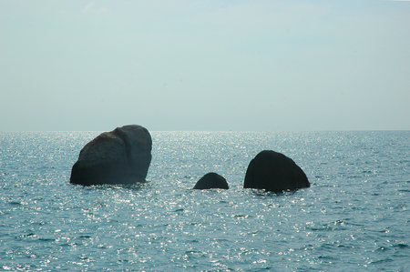 Three rocks are surrounded by an ocean which sparkles under the sunshine. The water is calm, and the sky has faint white clouds. A boat can just be seen on the horizon.