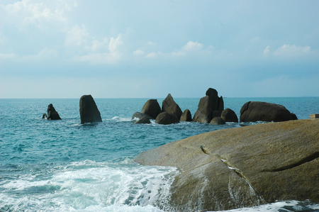 Waves have broken over a flat rock, covering it in white water. A cluster of dark vertical rocks stand in the sea behind. The water is calm. The sky is blue, with faint white clouds.