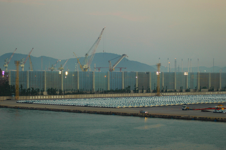 Rows of cars at a shipping terminal, awaiting delivery. Cranes and moving equipment tower over a fence, with hills in the background. The sun is just rising. One car has headlights turned on.