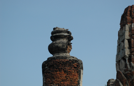 Closeup of ruins in a temple in Thailand. Much of the grey stone has been removed, revealing rough red bricks. The remains of an urn beside a large tower are visible against a clear blue sky.