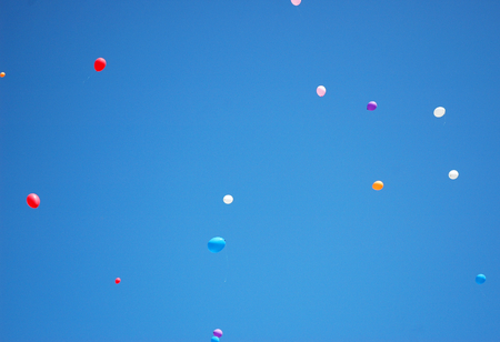 Balloons of all colours have been released and are floating in a clear blur sky. A few white strings attached to the balloons can be seen. Stock Photo