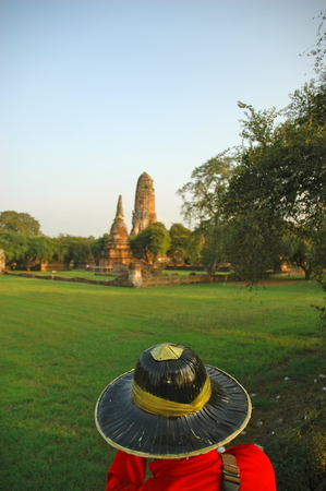 A view over the head of a mahout guiding an elephant to temple ruins. The mahout is traditonally dressed in a bright red shirt and a black hat. Green lawns stretch to the ruins. The sky is blue.