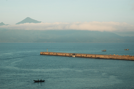 Low-lying clouds stretch over a harbour. A mountain in the background rises above the clouds to a clear blue sky. Some small fishing boats are on either side of a stone breakwater.