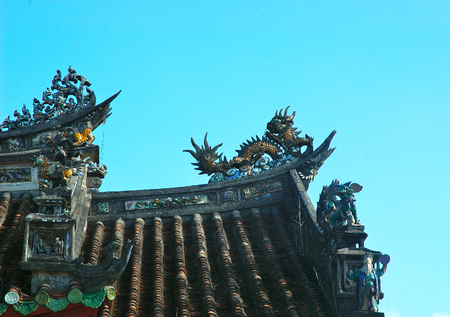 The corner of a roof on a Vietnamese temple is seen against a blue sky. Dragons and other details are visible. The roof is covered with traditional curved terracotta tiles.