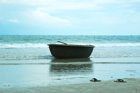 A traditional Vietnamese basket-boat is on the beach, with waves breaking around it. A pair of thongs (flip-flops) are on the sand. Flags mark channels in the water. The sky blue with clouds.