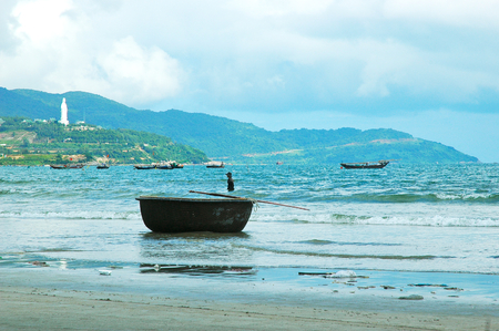 Traditional Vietnamese fishing boats near a beach, with a basket-shaped boat resting on the sand.