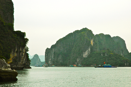 Boats and house-boat are dwarfed by limestone cliffs in Halong Bay, Vietnam. The houses are part of a floating village. The cliffs are covered in trees. The sky is overcast.