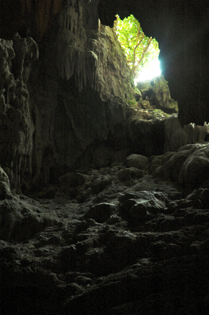 A shaft of sunlight lightens an underground cave