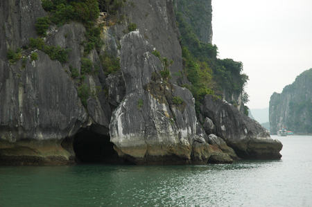 The entrance to a cave at the base of a limestone cliff, which rises from the ocean. Trees cover the rocks. Other cliffs are in the background. Some boats and houseboats are in the distance. The sky is overcast. The cliffs are in Halong Bay, Vietnam.