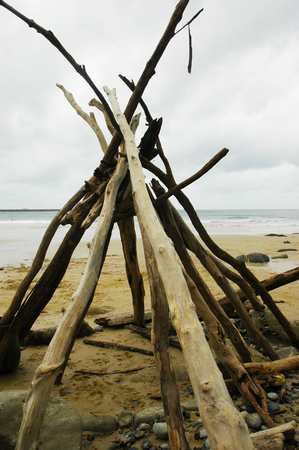 Long branches of driftwood have been stacked into a teepee-shape on a beach. Pebbles and stones are at the base. The sand stretches to a receeding tide, with a stone breakwater in the distance. The sky is overcast. A few swimmers are just visible.