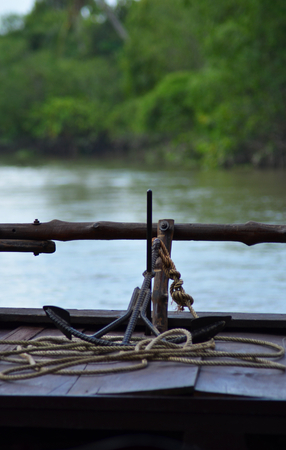 An anchor and rope rest on the back of a boat made from dark wood. A river flows past, boarded by the lush forest of the Mekong.