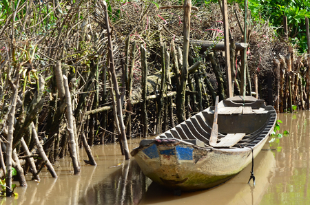 A traditional Vietnamese wooden boat anchored at the edge of a muddy river. Wooden poles form a barrier against the forest and act as a mooring for the boat. An oar is resting in the boat.
