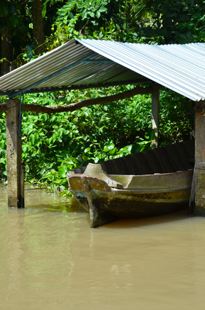 A wooden boat is moored under a make-shift shelter on a muddy branch of the Mekong River. The shelter has a corrogated iron roof. Trees cover the waters edge. Stock Photo